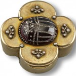 Wedding present to Queen Mary from the members of the British Embassy in Berlin Silver-gilt, straight-sided, quatrefoil-shaped box, with hinged lid, mounted with a red glass and diamond-set scarab and four stylised fleurs-de-lys